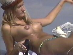 Rubia con pezones hinchados topless en la playa