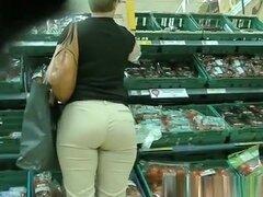 Mujer de culo grande en pantalones apretados, mujer de gran culo en pantalones ajustados y pelo corto, compra algunas cosas en el supermercado.
