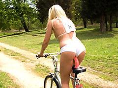 Rubia de increible cuerpo realiza un viaje en una inusual bicicleta al aire libre