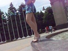 Chica joven en un vestido azul sentado en la fuente, chick adolescente quiere hacer unas fotos inocentes cerca de la fuente. Su amiga tomó algunas fotos y fue demostrando nos wat se oculta bajo la falda.