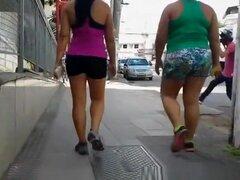 Más delgadas y más gordas chicas en shorts apretados deportes, más delgadas y más gordas chicas en apretado deportes pantalones cortos paseando por ciudad en rápido ritmo.