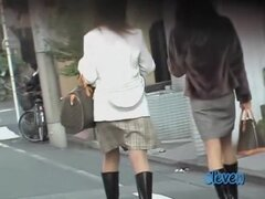 Chicas asiáticas tienen sus faldas tirados por una calle sharker., par de amigas japonesas hermosas caminando sobre la acera Haz molestado por un sharker calle caliente. Logra levantar tanto sus faldas antes que persecución lejos.