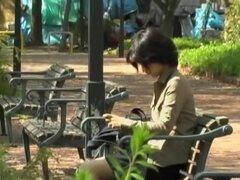 Video de sharking falda salvajes en un parque público en Japón, Adorable chica japonesa se sienta en un banco del parque sin saber que será una estrella en un video de sharking. Hombre corre detrás de ella y levanta su falda. Se revelan su sexy bragas azu