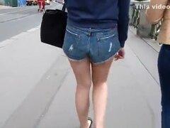 Chica en pantalones cortos azules, muchacha en pantalones cortos azul a pasear por la ciudad.